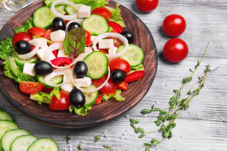 Traditional greek salad with fresh vegetables, feta cheese, black olives, and ingredients for cooking Greek salad oil, thyme, cherry tomatoes, cucumbers, salt