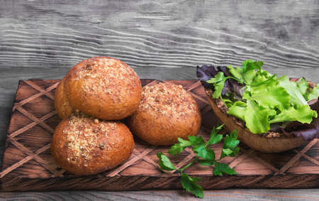 grit: Freshly baked bread and rolls grain grit, lettuce salad, parsley on a board on a gray wooden background in rustic style