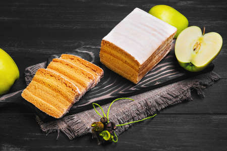 pastila: apple biscuit pie pieces, fresh apples, three slices cut biscuit pie on a cutting board on a black wooden background surface Stock Photo