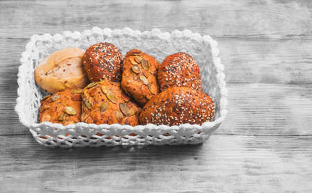 flax seeds: Three homemade rye buns with grit poppy, sesame and flax seeds, three rye buns with pumpkin seeds, homemade bun made with white flour in a white knitted basket on a light wooden background in the style of Shabby Chic