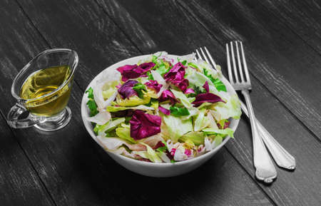 escarole: Italian salad with freshly harvested organic vegetables including varieties of lettuce Iceberg, Radic, Frisse with Italian dressing for salad of lettuce, silver forks on a dark black wooden background