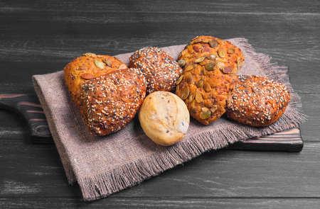 Three homemade rye buns with grit poppy, sesame and flax seeds, three rye buns with pumpkin seeds, homemade bun made with white flour, burlap cloth, on dark black wooden background Stock Photo
