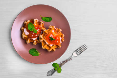Freshly soft thick Belgian waffles with apricot jam, mint leaves, cream, silver fork on a white plate on a brown wooden background, top view