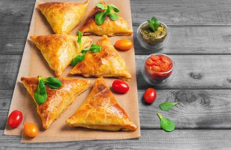 pakistani food: Delicious deep fried south Indian Samosa pies with meat, lettuce, mint chutney and tomato sauce on gray wooden background in rustic style, empty place for text, recipe Stock Photo