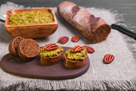 caterers: Italian pesto sauce, bagget, small sandwiches bruschetta, pecans on a black wooden background surface