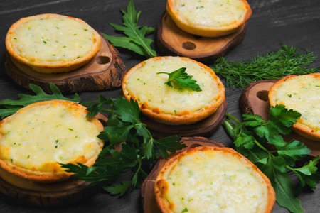 logwood: Little mini pizza tartlets with cheese and fresh herbs, lettuce, dill, parsley on a dark black background wooden surface