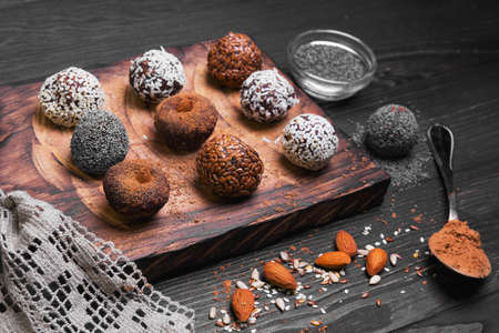 Sweets handmade chocolates sweet-stuff candies, sprinkled poppy, coconut, linseed, sesame, cocoa, almonds oerhi on cutting board with lace on light wooden background in rustic style