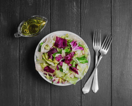 escarole: Italian salad with freshly harvested organic vegetables including varieties of lettuce Iceberg, Radic, Frisse with Italian dressing for salad of lettuce, silver forks on dark black wooden background Stock Photo