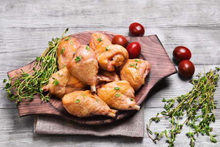 white backing: Chicken poultry meat legs drumstick with thyme seasoning, fresh thyme on sackcloth, cherry tomatoes on light shabby white wooden background, top view