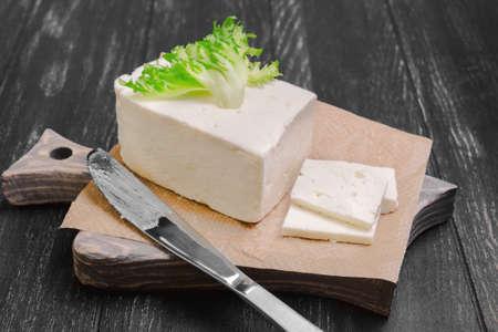 ewes: Pickled sheep cheese feta Sirtaki, knife, lettuce on  cutting board on dark black wooden background Stock Photo