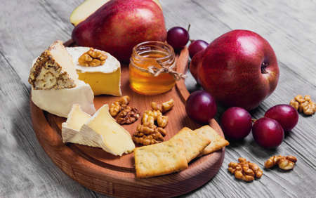 Fruit pear whole, grapes, pear cut in half, cheese. Camembert cheese, goat cheese, honey, walnuts on light white wooden background