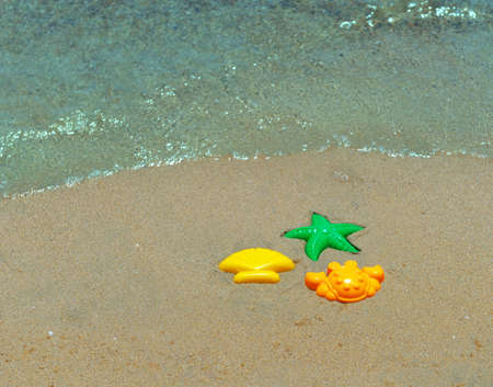 golden shovel: Three childrens plastic forms for playing with sand, green starfish, shell yellow, orange, crab, sand Beach, sea