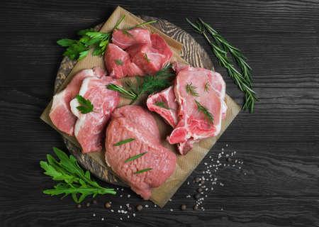 Verschillende assortiments assortiments van besnoeiingen en gedeelten van ruw vers rood vleesvarkensvlees dat met verse kruiden, kruid, bruine houten achtergrond wordt getoond