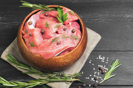 Slices of pork stew in wooden bowl on sacking with spices and herbs on black wooden background Stock Photo