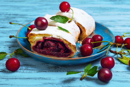 filo pastry: Cake cherry roll filled strudel pieces in blue ceramic plate, fresh cherries for strudel, blue wooden background, rustic style