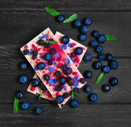 Chocolate bars White, blackberries, blueberries, blueberry, raspberry, candied violet petals, mint leaves, candy heart on dark black background wooden surface, empty place for text, top view