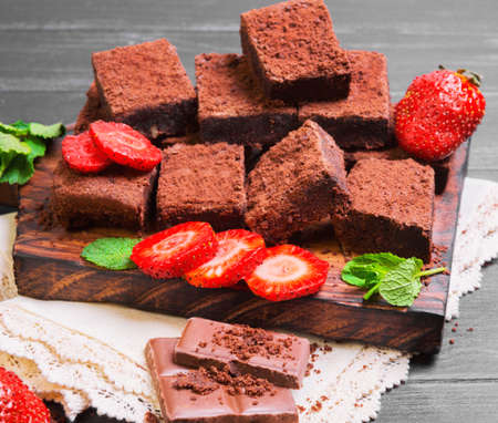 Pieces of chopped chocolate cake brownie with nuts, chocolate bars, leaves and sprigs of mint, strawberry berries on cutting board, black wooden background