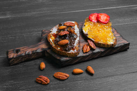 pecans: Sweet dessert sandwiches crostini with lemon jam, plums, pecans, hazelnuts, almonds, rye bread on a cutting board on a black wooden background, empty place for text