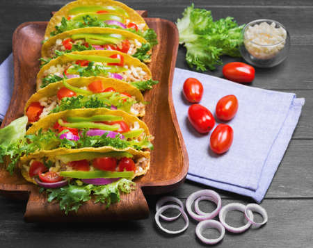 Mexican food tacos, peppers, cherry tomatoes, grated cheese, minced meat in a corn tortilla on tray, linen towel, black wooden background Stock Photo