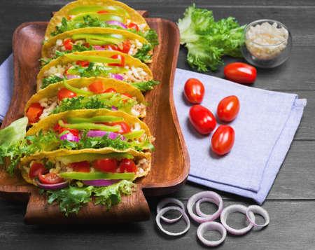 tortilla de maiz: Tacos mexicano de comida, pimientos, tomates cherry, queso rallado, la carne picada en una tortilla de maíz en bandeja, toalla de lino, madera de fondo negro