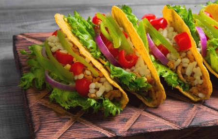 tortilla de maiz: Tacos mexicano de comida, pimientos, tomates cherry, queso rallado, la carne picada en una tortilla de maíz en bandeja, fondo gris de madera rústica