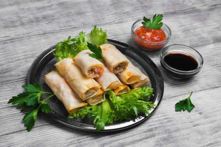 Little spring rolls on round metal tray plate, light white surface, lettuce, parsley greens, Fresh green onions, soy sauce, tomato sauce