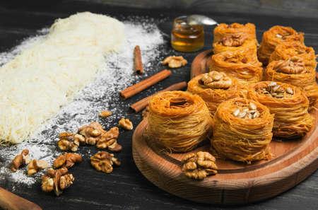 Cooking sweets turkish traditional ramadan pastry dessert kunafa kadaif, baklava , ingredients dough, nuts, walnuts, peanuts, sunflower seeds, honey, cinnamon, dark black wood background