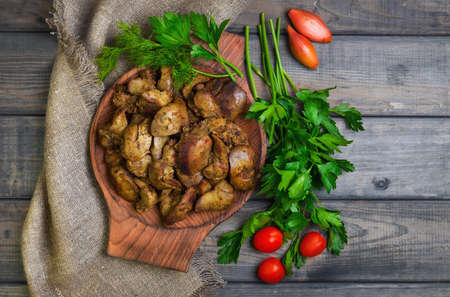 higado de pollo: Stewed chicken liver, additional ingredients for chicken liver parsley, dill, cherry tomatoes, shallot, gray wooden background, rustic style, top view