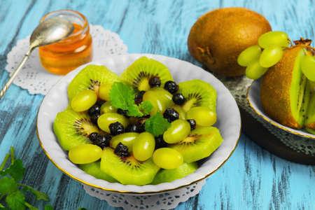 Fruit and berry salad. Ingredients for salad of kiwi, blueberry, grape, Melissa, honey. Kiwifruit on white saucer. Blue wood background. Stock Photo