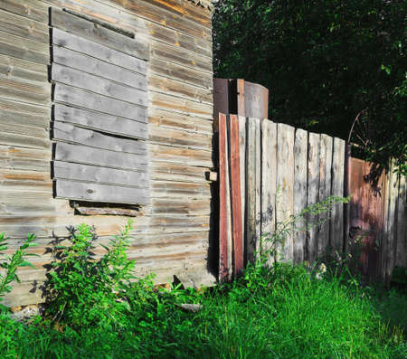 rickety: Old brown-gray abandoned wooden country house with boarded up windows, rickety fence, green grass and trees, metal gate, summer