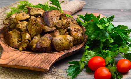 higado de pollo: Stewed chicken liver, additional ingredients for chicken liver parsley, dill, cherry tomatoes, shallot, gray wooden background, rustic style Foto de archivo
