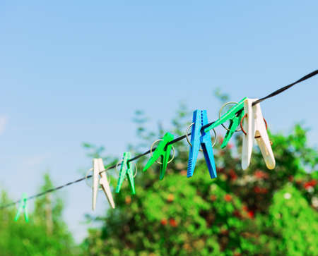 Plastic clothespins laundry hook colorful rope.Village plastic pegs. Two white clothes pins, one blue clothespin rope on focus, four green clothespins. Summer rural landscape.