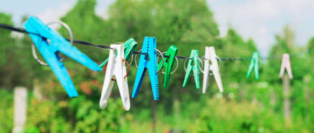 Plastic clothespins laundry hook colorful rope.Village plastic pegs. Three white clothes pins, two blue clothespin rope on focus, four green clothespins. Summer rural landscape. Stock Photo