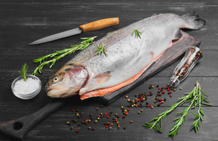 gutted: Cutting gutted red fish trout sweetfish on board, spices trout rosemary, different kinds of peppers, salt, dark black wood background, rustic style Stock Photo