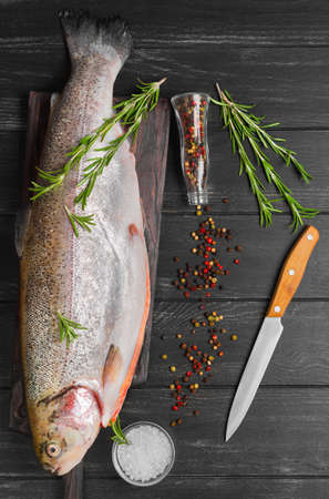 gutted: Cutting gutted red fish trout sweetfish on board, spices trout rosemary, different kinds of peppers, salt, dark black wood background, rustic style, top view