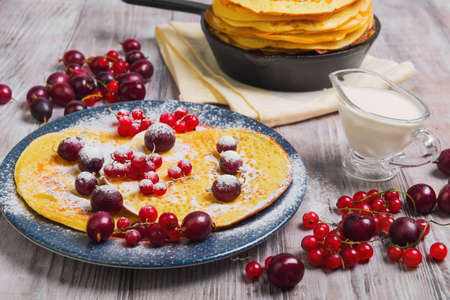 papas doradas: Pancakes fritters in cast iron skillet stack, hash browns pancakes on plate with berries. Berries for pancakes crepes red currants, gooseberries, cherries, sour cream. Light white wooden background.