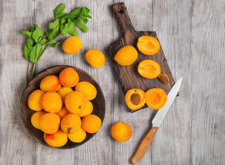 Fresh ripe apricots on wooden plate, mint leaves, fruits apricots on cutting board, cut apricots in half. Light white rustic wood background. Top view.