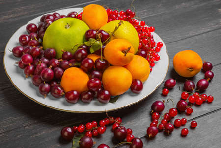White plate with an assortment of fresh garden fruits and berries. Fruits apricot, apple, pear. Berries red currants, cherries, gooseberries. On dark black wooden table fruit and gooseberries, apricots, red currants, cherries.