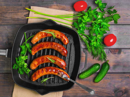 Grilled fried sausages kupaty on a cast iron skillet grill, greens to grilled fried sausages parsley, thyme, rosemary, tomatoes, cucumbers. Fork for fried sausages. Grey wooden background. Top view. Stock Photo