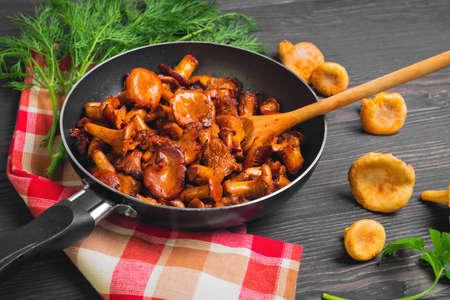 캐서린 프라이팬에서 볶은 살구 버섯, 볶은 살구 파슬리, 딜, 천을위한 허브. 나무 테이블의 어두운 갈색 배경에 원시 chanterelles. 스톡 콘텐츠