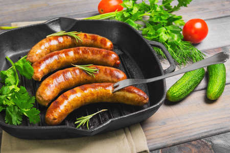 Grilled fried sausages kupaty on a cast iron skillet grill, greens to grilled fried sausages parsley, thyme, rosemary, vegetables, tomatoes, cucumbers. Fork for fried sausages. Grey wooden background. Stock Photo