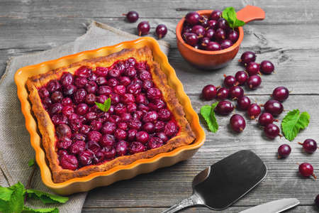 scapula: Fresh baked pie pastry with red berries of gooseberry in  square ceramic form, ripe berries of gooseberry for pie in bowl, gooseberries on gray wooden table background, mint, scapula for pies