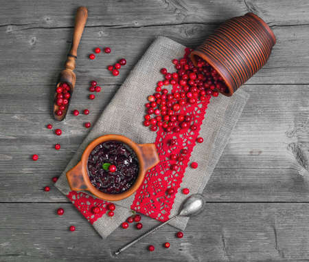 Homemade Lingonberry cranberry cowberries sauce. Fresh berries Lingonberry cranberries cowberries in ceramic cup. Lingonberry on table. Grey rustic wooden background. Top view Imagens