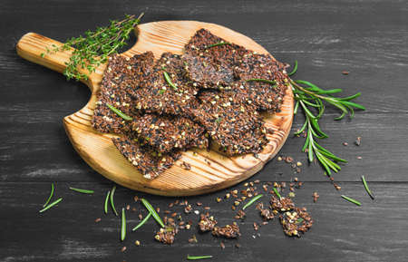 Bread crackers from grain flax seeds, sesame, spices, wooden board, healthy food. Broken pieces grain Bread crackers flax seeds. Spices for flax crackers grain breads thyme, rosemary. Black background