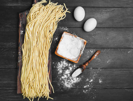 recipe background: Homemade Uncooked pasta spaghetti noodles on board. Ingredients for home-made spaghetti noodles chicken eggs, flour. The dark black wood background. Top view, blank space.