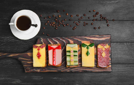 Breakfast for men. Figured sandwiches, coffee. Sausage sandwiches, cheese, vegetables. Concept Breakfast for the day men, father's day, business lunch. Dark black wood background. Top view.