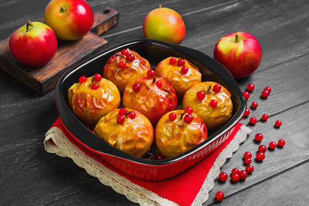 baked meat: Baked apples baking in oven. Fresh apples for baking on board. Caramel sauce for baked apples, red berries. Dark black wood background. Garden apples.