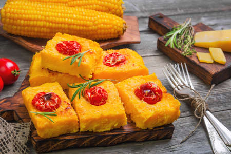Pieces Corn polenta baked with cherry tomatoes, Parmesan cheese on board. Boiled corn on wooden plate for polenta. Green for corn polenta thyme, rosemary. Gray wooden background. Stock Photo