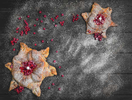 Sweet pastry buns in the form of Christmas snowflakes with powdered sugar. The dark black wood background. Concept with snow for Christmas cards. Red berries of cranberry buns for snowflakes. Top view, blank space.
