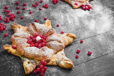 Homemade Sweet pastry buns in form of Christmas snowflakes, powdered sugar. Dark black wood background. Concept snow for Christmas cards. Red berries of cranberry buns for snowflakes.